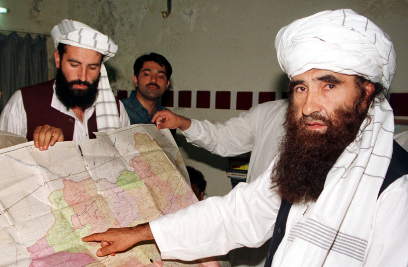 FILE PHOTO: Jalaluddin Haqqani points to a map of Afghanistan during a visit to Islamabad, Pakistan while his son Naziruddin looks on in 2001 (photo credit: REUTERS/STRINGER/FILES)