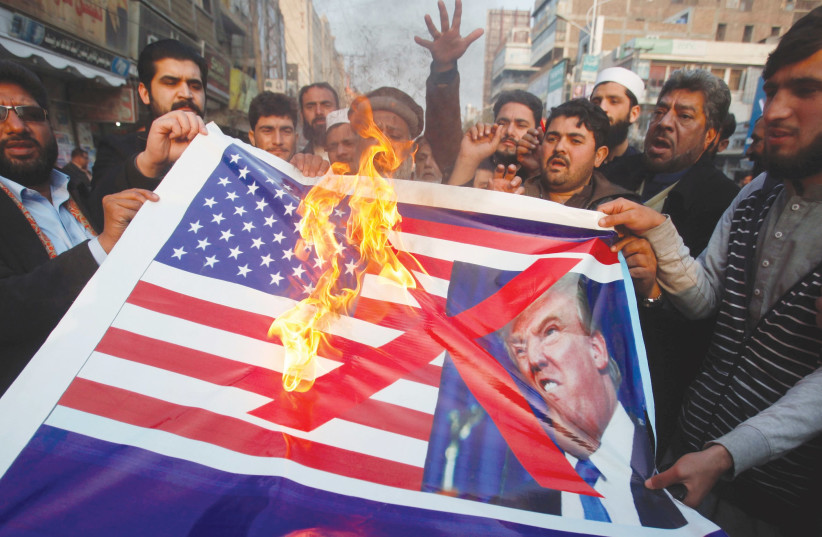 PEOPLE BURN a sign depicting a US flag and a picture of US President Donald Trump as they take part in a rally in Peshawar, Pakistan, last week. (Fayaz Aziz/Reuters) (photo credit: REUTERS/ FAYAZ AZIZ)