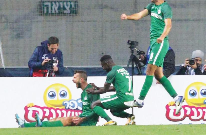 Maccabi Haifa players Nikita Rukavytsya (left), Sintiyahu Salalik (center) and Mohammed Awad celebrate during last night's win over Hapoel Tel Aviv on penalties in the State Cup round-of-32. (photo credit: ADI AVISHAI)