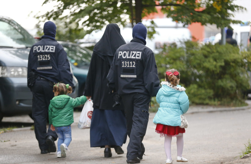 German security forces walk with a Muslim family outside a mosque in Berlin (photo credit: HANNIBAL HANSCHKE/REUTERS)
