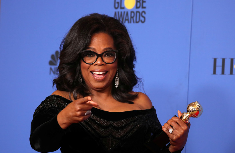 Oprah Winfrey poses backstage with her Cecil B. DeMille Award (photo credit: LUCY NICHOLSON / REUTERS)