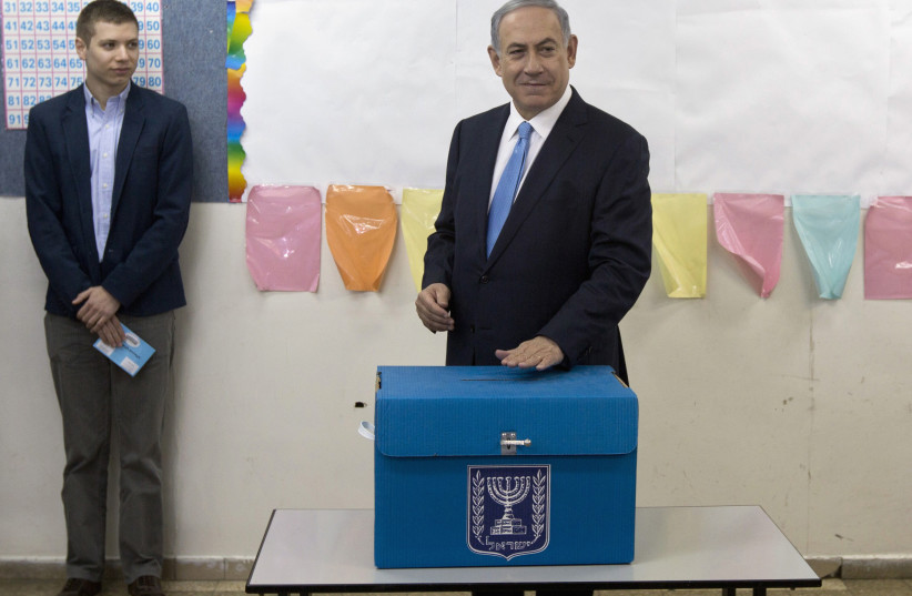 Prime Minister Benjamin Netanyahu casts his ballot for the parliamentary election as his son Yair stands behind him at a polling station in Jerusalem March 17, 2015. (photo credit: REUTERS/SEBASTIAN SCHEINER/POOL)