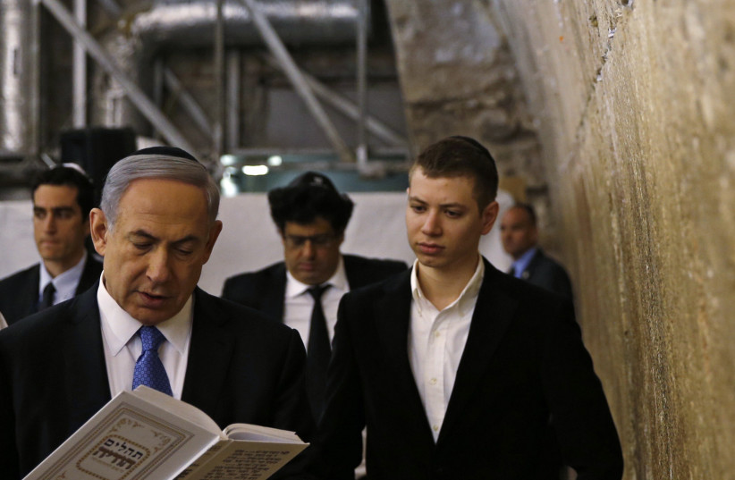 Yair Netanyahu observes his father Israeli Prime Minister Benjamin Netanyahu reading a prayer at the Western Wall in Jerusalem's Old City (photo credit: RONEN ZVULUN/REUTERS)