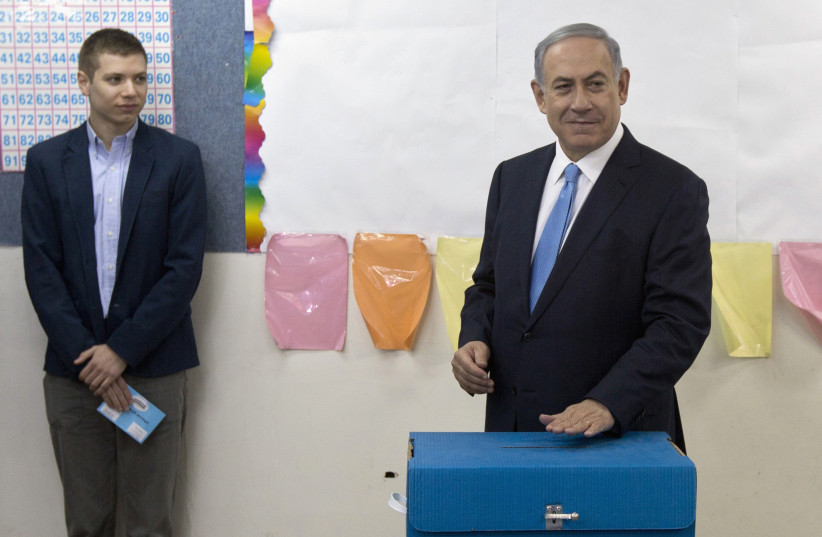Yair Netanyahu observes his father Israeli Prime Minister Benjamin Netanyahu casting a ballot in the 2015 elections. (photo credit: REUTERS/SEBASTIAN SCHEINER/POOL)