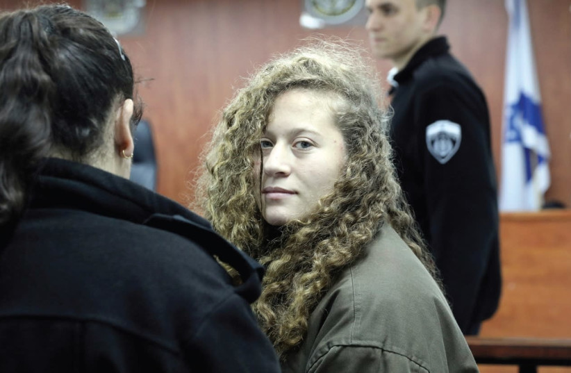 Ahed Tamimi (center) enters a military courtroom at Ofer Prison near Ramallah on New Year's Day. (photo credit: AMMAR AWAD/REUTERS)