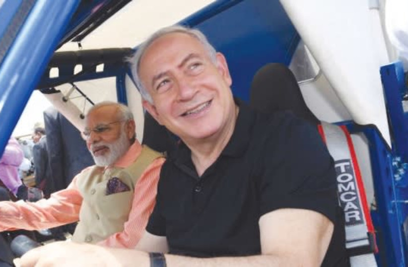 Prime Minister Benjamin Netanyahu and Indian Prime Minister Narendra Modi ride in a GalMobile water desalination and purification jeep at Olga Beach last July (photo credit: KOBI GIDEON/GPO)