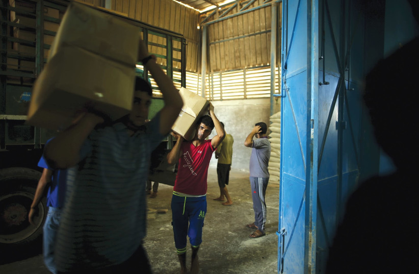 WORKERS CARRY boxes containing food supplies for Palestinian refugees at a United Nations Relief and Work Agency (UNRWA)-run food distribution center in Gaza in 2015. (photo credit: MOHAMMED SALEM/ REUTERS)
