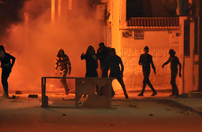 Tunisian protestors throw stones towards security forces in Tunis' Djebel Lahmer district early on January 10, 2018 (photo credit: SOFIENE HAMDAOUI / AFP)