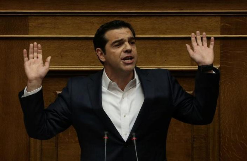 Greek Prime Minister Alexis Tsipras gestures as he addresses lawmakers before a parliamentary vote in Athens, Greece, May 18, 2017. (photo credit: ALKIS KONSTANTINIDIS / REUTERS)