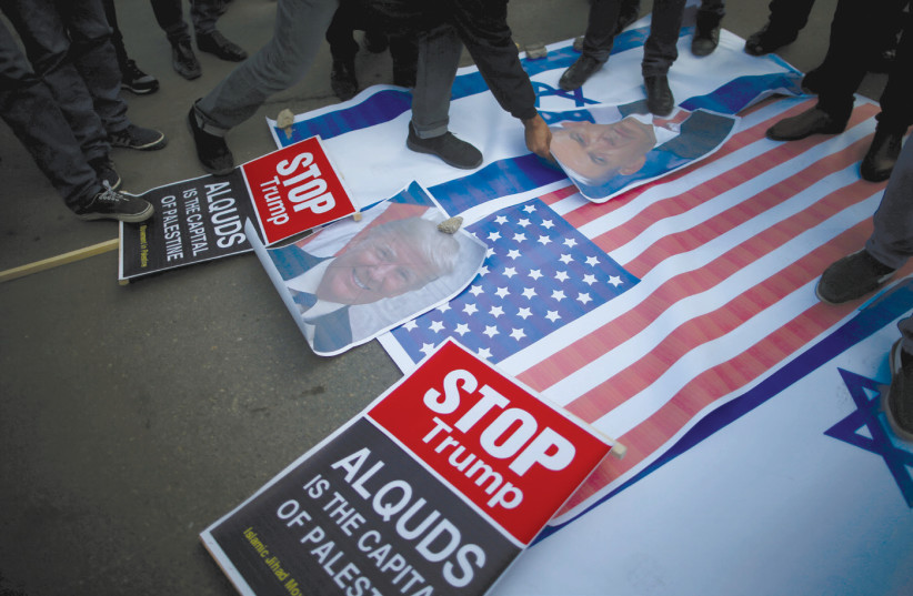 PROTESTERS IN Gaza City begin stomping on posters depicting Prime Minister Benjamin Netanyahu and US President Donald Trump and Israeli and American flags before burning them during a protest following Trump's recognition of Jerusalem as the capital of Israel. (photo credit: MOHAMMED SALEM/REUTERS)