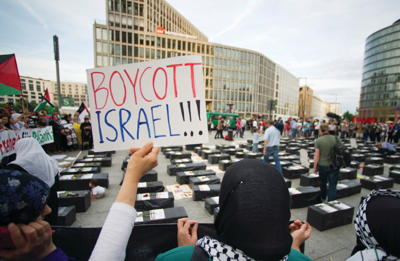A WOMAN holds a 'Boycott Israel' sign in front of symbolic cof ns while attending a demonstration in 2014 supporting Palestine, in Berlin (photo credit: STEFFI LOOS /REUTERS)