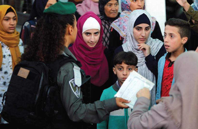 Palestinians wait to cross an Israeli checkpoint in Bethlehem last year. (Mussa Qawasma/Reuters) (photo credit: MUSSA QAWASMA / REUTERS)