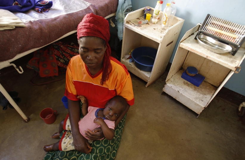 A Zambian woman holds her child at the paediatric section of the General Hospital in Livingstone (FILE) (photo credit: REUTERS/THIERRY ROGE)