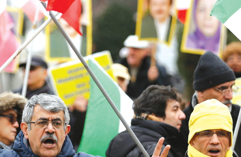 A WOMAN chants slogans during a protest against the visit of Iran's Foreign Minister Mohammad Javad Zarif, outside the European Union Council in Brussels. (Francois Lenoir/Reuters) (photo credit: REUTERS/FRANCOIS LENOIR)