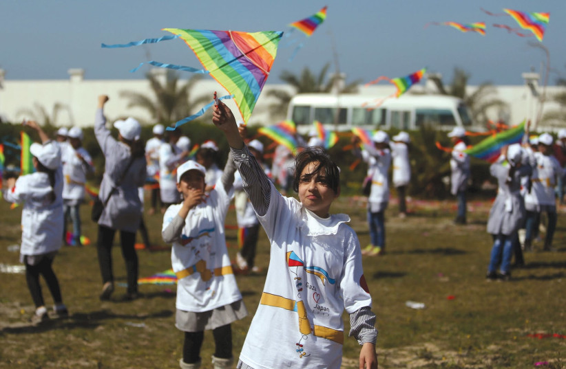 PALESTINIAN SCHOOLGIRLS fly kites to show solidarity with the Japanese people during an event organized by UNRWA to mark the anniversary of the March 11, 2011 earthquake and tsunami, in Khan Yunis in the southern Gaza Strip, in 2017. (photo credit: IBRAHEEM ABU MUSTAFA / REUTERS)