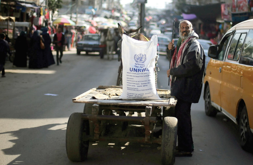 A MAN STANDS next to a cart carrying a sack of flour distributed by UNRWA in the Khan Yunis refugee camp in the Gaza Strip in January, 2018. (photo credit: IBRAHEEM ABU MUSTAFA / REUTERS)