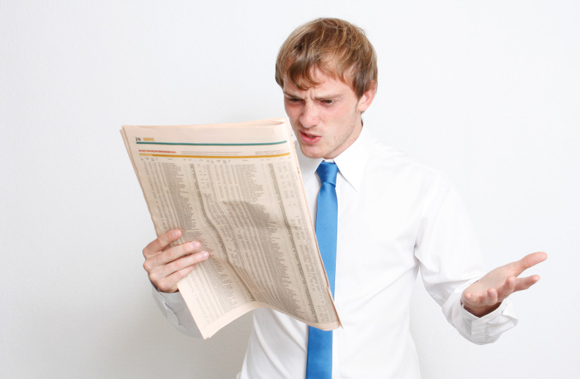 Man reads newspaper in frustration. (photo credit: INGIMAGE)