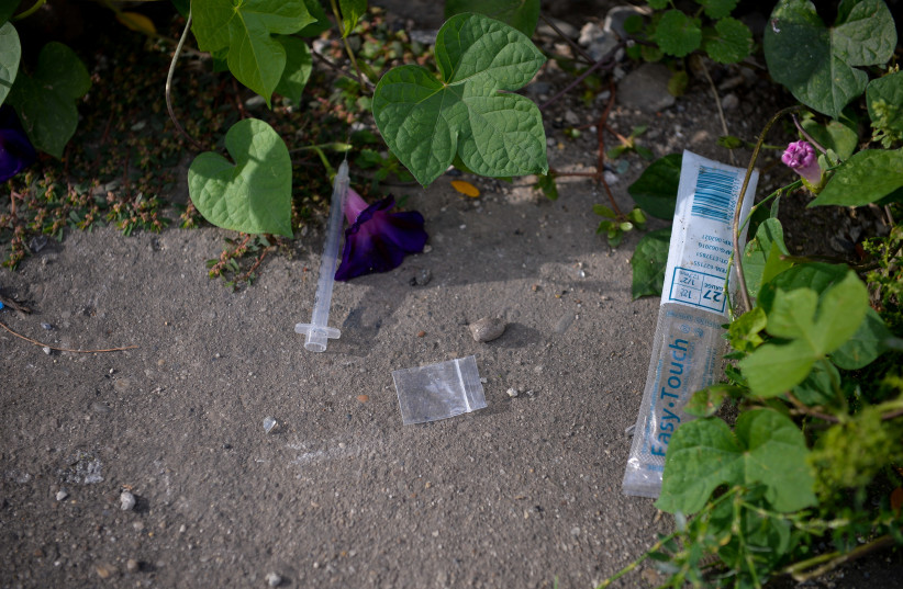 A needle used for shooting heroin and other opioids and an empty bag litter the ground in the Kensington section of Philadelphia, Pennsylvania, U.S. October 26, 2017. (photo credit: REUTERS/CHARLES MOSTOLLER)