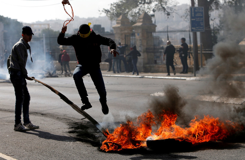 A Palestinian demonstrator jumps over a burning tire in a protest in Bethlehem, January 2018 (photo credit: MUSSA QAWASMA / REUTERS)