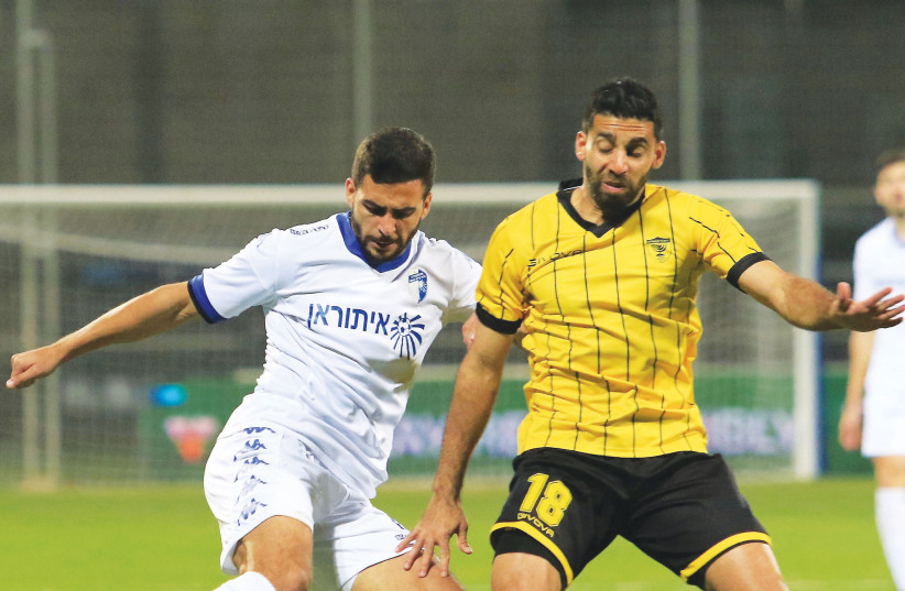 Beitar Jerusalem midfielder Hen Ezra (right) battles for the ball with Ironi Kiryat Shmona's Ahmed Abed (left) during a 1-1 draw in Premier League action. (photo credit: ERAN LUF)