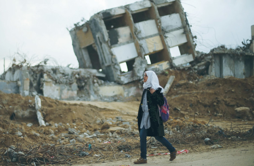A GIRL WALKS by the remains of a house in the northern Gaza Strip that was destroyed during Operation Protective Edge. (photo credit: MOHAMMED SALEM/REUTERS)