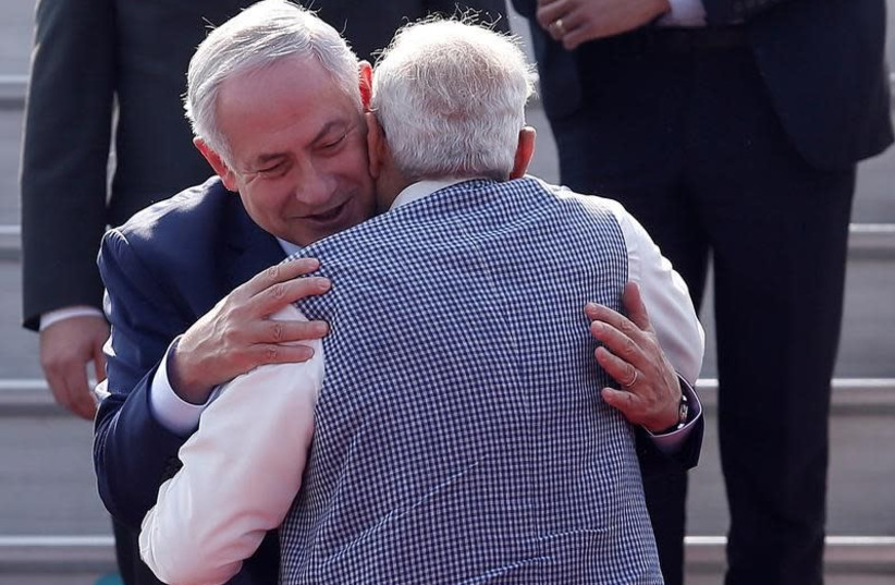 DATE IMPORTED: January 14, 2018 Israeli Prime Minister Benjamin Netanyahu and his Indian counterpart Narendra Modi hug each other upon Netanyahu's arrival at Air Force Station Palam in New Delhi, India, January 14, 2018. (photo credit: ADNAN ABIDI/ REUTERS)