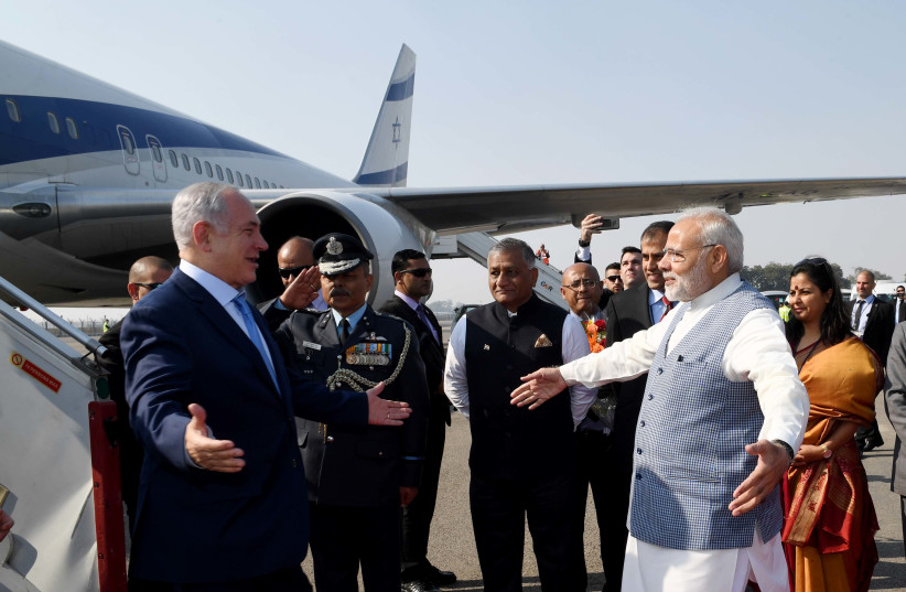 Prime Minister Benjamin Netanyahu is greeted with a hug by Indian Prime Minister Narendra Modi upon arrival in India, January 14, 2018  (photo credit: AVI OHAYON - GPO)
