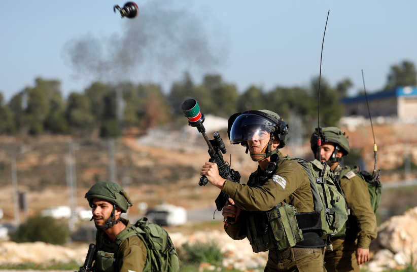 An Israeli soldier fires tear gas at Palestinian demonstrators during clashes at a protest calling for the release of Palestinian prisoners from Israeli jails, in the West Bank village of Nabi Saleh, near Ramallah January 13, 2018. (photo credit: MOHAMAD TOROKMAN/REUTERS)