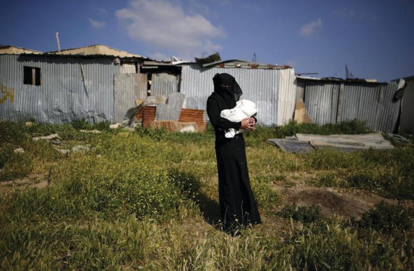 Une femme bédouine tenant son bébé (photo credit: REUTERS/AMIR COHEN)