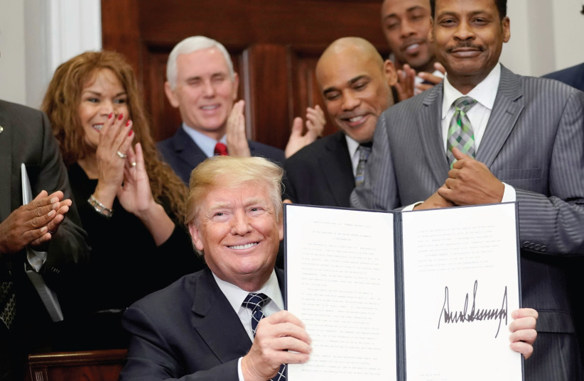 US President Donald Trump holds up a proclamation honoring Martin Luther King Jr. in the White House in January of 2018 (photo credit: JOSHUA ROBERTS / REUTERS)