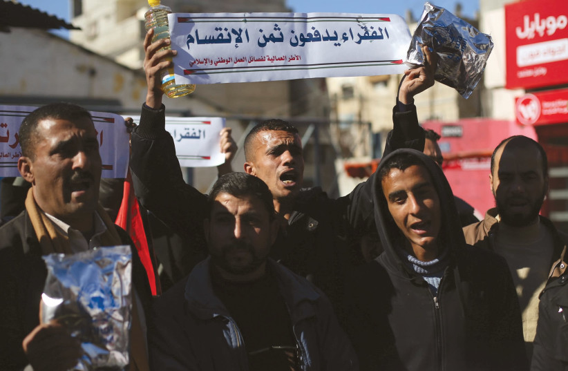 Palestinians protest poor living conditions at UNRWA's Rafah office in the southern Gaza Strip. (Sign: The poor pay the costs of division) (photo credit: RADI RUBINSTEIN)