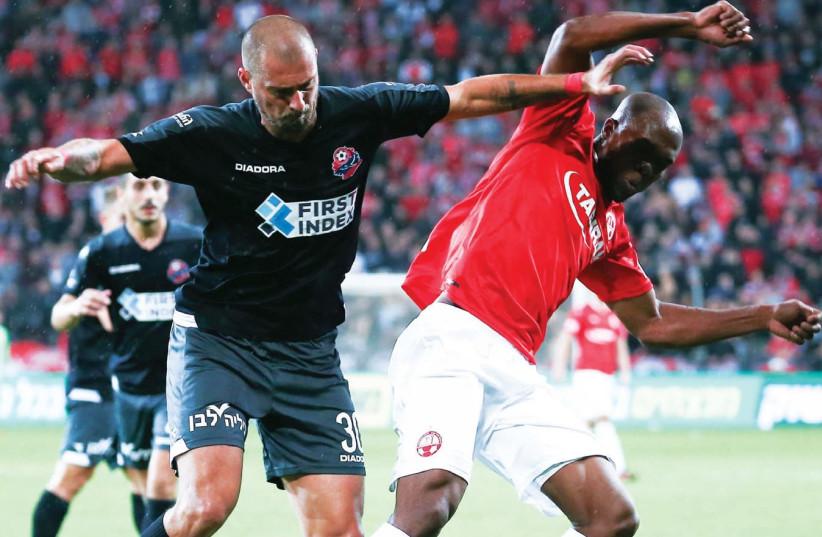 Hapoel Beersheba forward Anthony Nawkaeme (right) battles for the ball with Hapoel Haifa defender Gabriel Tamas during last night's 1-1 draw at Turner Stadium (photo credit: DANNY MARON)