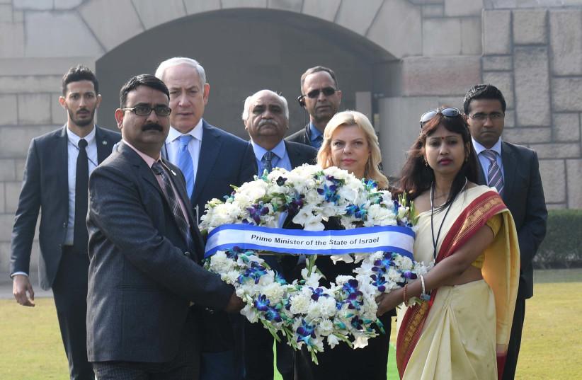 Israeli PM Netanyahu and Israeli First Lady present a reef for the memorial of Mahatma Gandhi. (photo credit: AVI OHAYON - GPO)