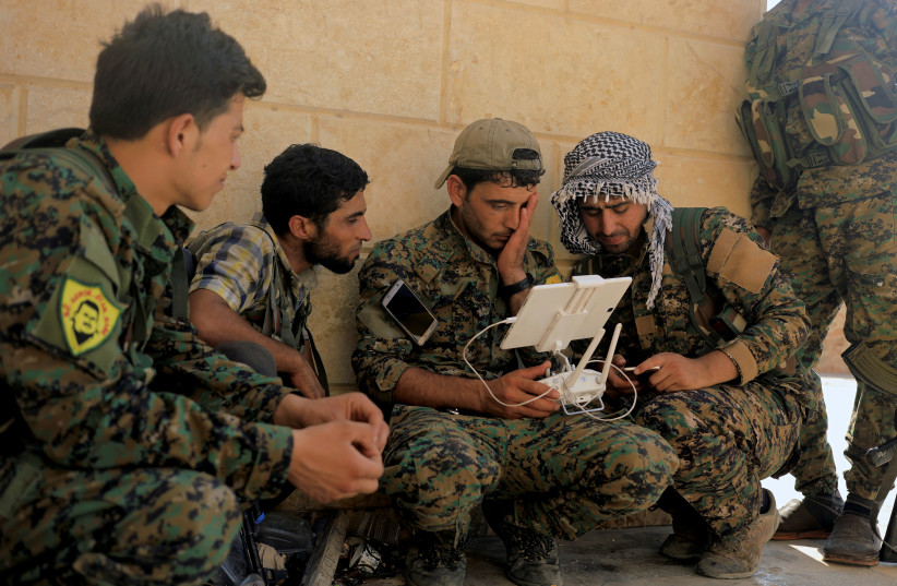 Members of the Syrian Democratic Forces control the monitor of their drone at their advanced position in a a district of Raqqa, Syria.  (photo credit: REUTERS)
