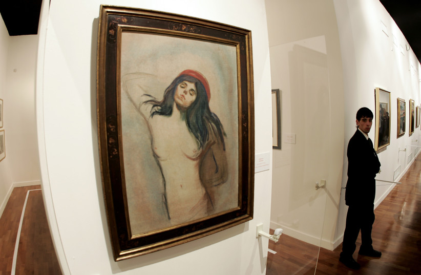 """A security guard stands near a painting of """" Madonna"""" by Norwegian artist Edvard Munch (photo credit: REUTERS/ALESSANDRO BIANCHI)"""
