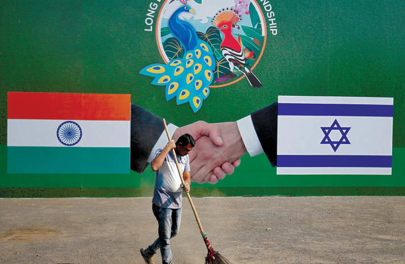 A municipal worker cleans the street in front of a bilboard displaying Indian and Israeli flags for PM Netanyahu's visit, Ahmedabad, India, January 2018 (photo credit: REUTERS/AMIT DAVE)