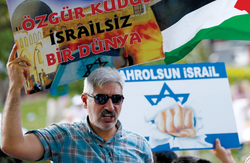 ANTI-ISRAEL protesters hold placards and a Palestinian flag during a demonstration to mark the annual al-Quds Day in Istanbul in July 2016. The placards read, 'Free Jerusalem, a World without Israel' (left) and 'Down with Israel.' (photo credit: MURAD SEZER/REUTERS)
