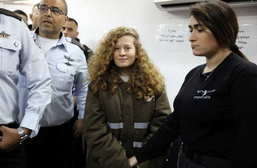 Palestinian teen Ahed Tamimi enters a military courtroom escorted by Israeli security personnel at Ofer Prison, near the West Bank city of Ramallah, January 15, 2018. (REUTERS/Ammar Awad) (photo credit: AMMAR AWAD / REUTERS)