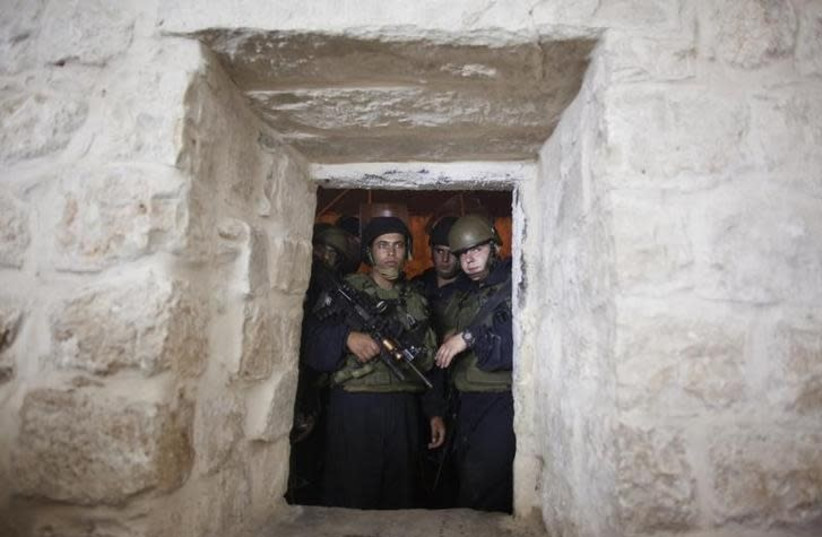 Israeli soldiers stand guard at a window hole at Joseph's Tomb as Jewish worshippers pray inside it, in the West Bank city of Nablus, early July 4, 2011 (photo credit: REUTERS/NIR ELIAS)