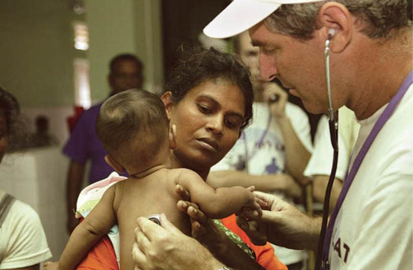 Le professeur Eli Schwartz de Tel Hashomer, spécialiste mondial des maladies tropicales, traite un enfant au Sri Lanka après le tsunami de 2004 (photo credit: Courtesy)