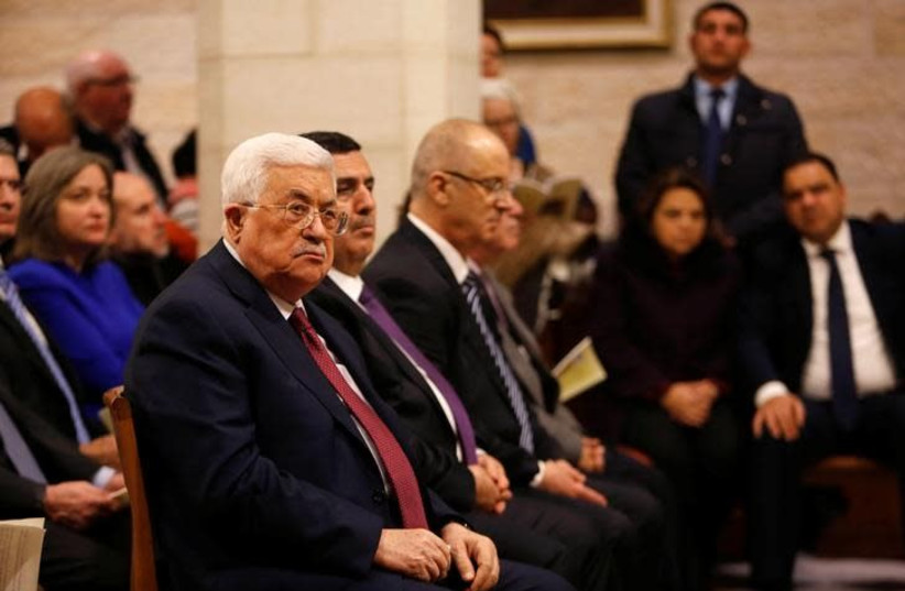 Palestinian President Mahmoud Abbas attends a Christmas midnight mass at the Church of the Nativity in the West Bank city of Bethlehem, December 25, 2017 (photo credit: MUSSA QAWASMA / REUTERS)