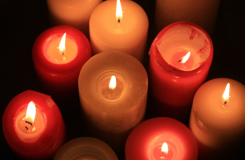 A group of burning candles in different colors. (photo credit: INGIMAGE)