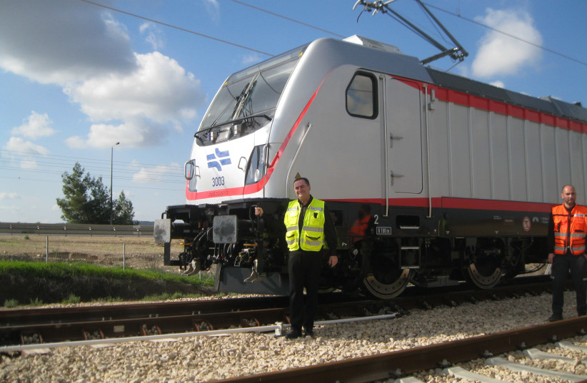 Transportation Minister Israel Katz stands next to the electric locomotive that hauled test train on January 15, 2018 (photo credit: SYBIL EHRLICH)
