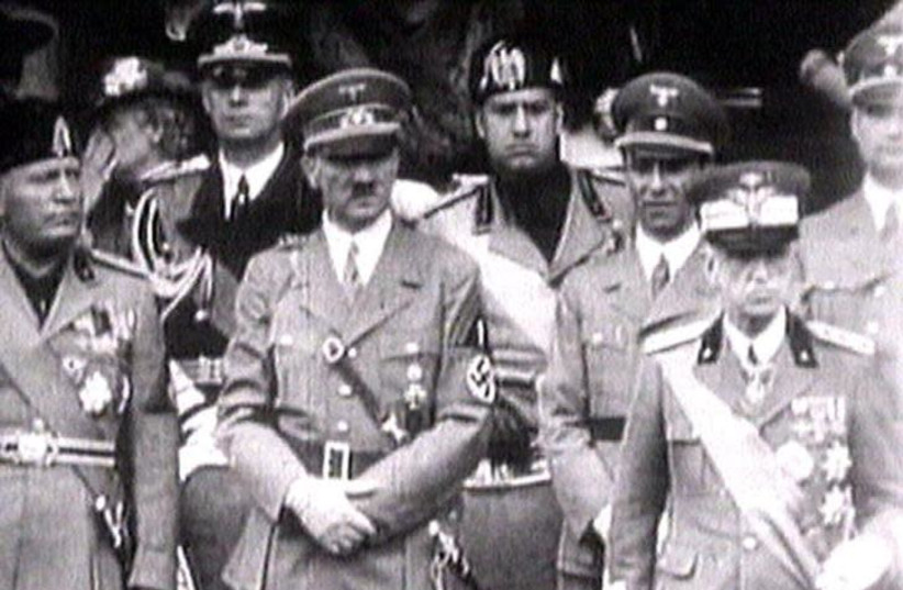 King Victor Emanuel III, (R) Adolf Hitler (C) and Benito Mussolini (L) watch fascist troops march past from a balcony in central Rome in this 1941 television file footage. (photo credit: REUTERS TV)