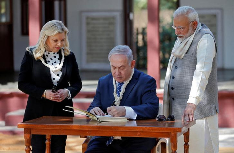 Israeli Prime Minister Benjamin Netanyahu writes a message in the visitor's book as his wife Sara and his Indian counterpart Narendra Modi look on during their visit to Gandhi Ashram in Ahmedabad, India, January 17, 2018.  (photo credit: REUTERS/AMIT DAVE)