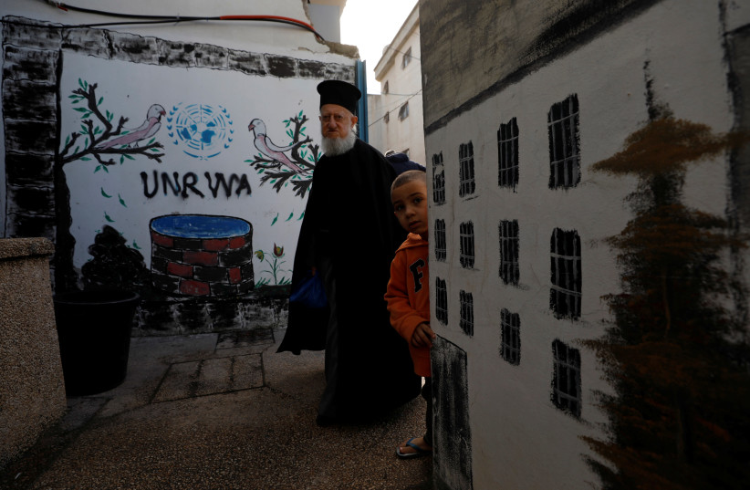 A Palestinian man walks past a logo of United Nations Relief and Works Agency (UNRWA) in Jalazone refugee camp, near the West Bank city of Ramallah January 3, 2018. (photo credit: MOHAMAD TOROKMAN/REUTERS)