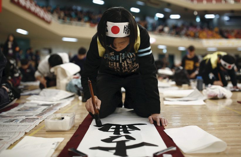 A GIRL participates in a calligraphy contest in Tokyo in 2016 (photo credit: THOMAS PETER/REUTERS)