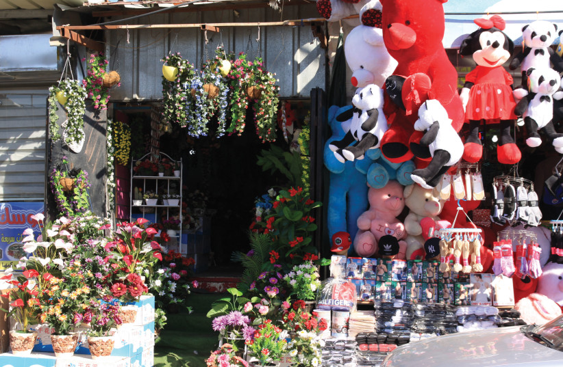 SHOPS IN Barta'a offer all sorts of kitsch, household goods, and clothing – toys, cosmetics, socks, plants, stuffed animals, plastic slippers and  oral head scarves (photo credit: FRANZISKA KNUPPER)