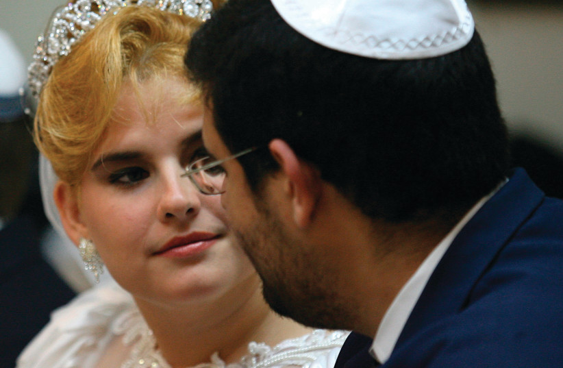 A COUPLE looks at each other while waiting to get married at Havana's Beth Shalom synagogue in 2007 (photo credit: CLAUDIA DAUT/REUTERS)