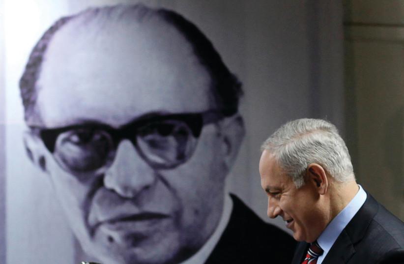 PRIME MINISTER Benjamin Netanyahu walks in front of a poster depicting the late prime minister Menachem Begin in Tel Aviv in 2010 (photo credit: REUTERS/NIR ELIAS)